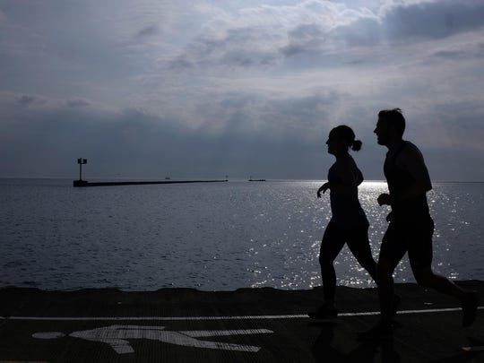 People jog along the shore of Lake Michigan Wednesday morning, June 13, 2018, in downtown Chicago.
