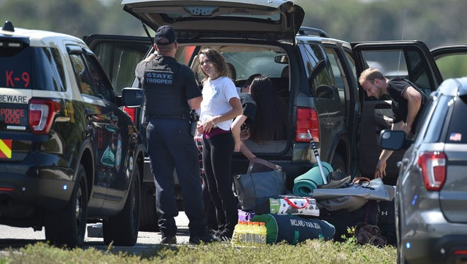 A Florida Highway Patrol officer talks with one of the four passengers in a car from Maryland after FHP finished searching their vehicle for drugs along Okeechobee Road near Matthews Road on Thursday, March 1, 2018, in western St. Lucie County. The group repacked their belongings after being searched and continued west towards Okeechobee. To see more photos, go to TCPalm.com.