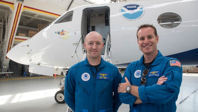 """NOAA Aircraft Commander Doug Macintyre and Lt. Junior Grade Billy Bonner pose in front of """"Gonzo,"""" their Gulfstream IV research jet."""