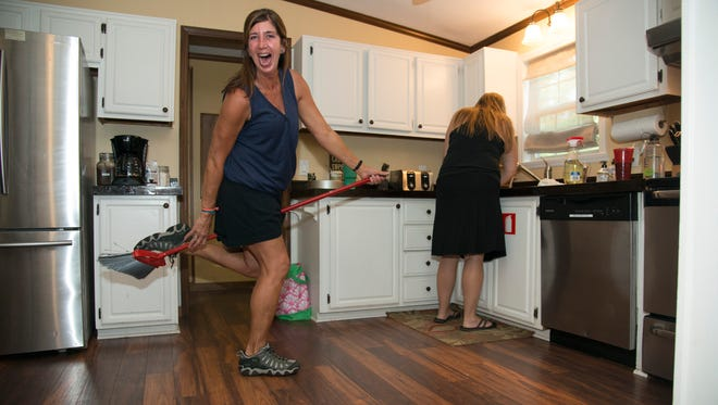Anita Kaschak cuts up during sweeping while Jackie Vale, right, cleans the counters of the Broad River house Vale rents out.