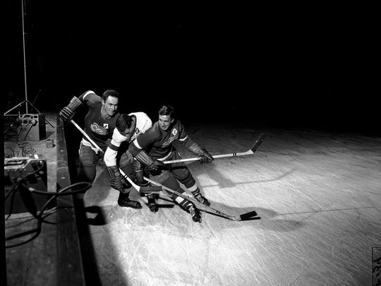 Red Kelly, left, and Ted Lindsay, right, battle for the puck at practice.