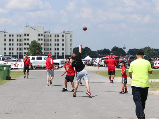 Kids toss a football as part of the tailgating festivities ahead of the Ragin' Cajuns football game.