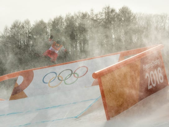 The wind blows snow across the course as a competitor practices before the Snowboard Ladies's Slopestyle Qualification was cancelled due to weather Sunday.