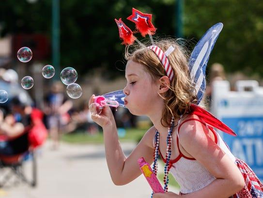 Ellie Lach, 5, of Pewaukee blows bubbles as she waits