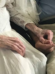 Arleen and Forrest Meyer clutch hands while being interviewed. Arleen put on her wedding dress from 75 years ago.