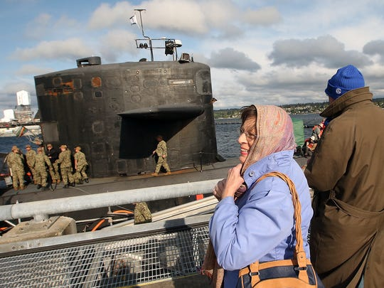 Cynthia Karottki tightens her head scarf against the wind as she and husband Hartmut watch the USS Bremerton for their sailor son Christoph to disembark at Naval Base Kitsap-Bremerton on Friday. The Karottkis traveled from Massachusetts to see their son.