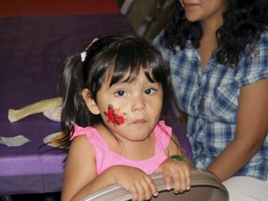 A young face-painted girl finishes a snack before heading back out for Fiesta fun at last year's Fiesta in Arendtsville.