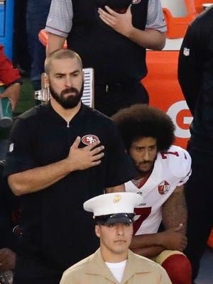 San Francisco 49ers quarterback Colin Kaepernick, middle, kneels during the national anthem before the team's NFL preseason football game against the San Diego Chargers, Thursday, Sept. 1, 2016, in San Diego.