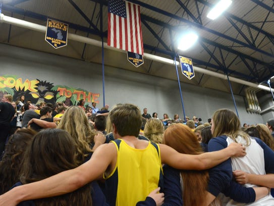 South Lyon High seniors lock arms as they stand for