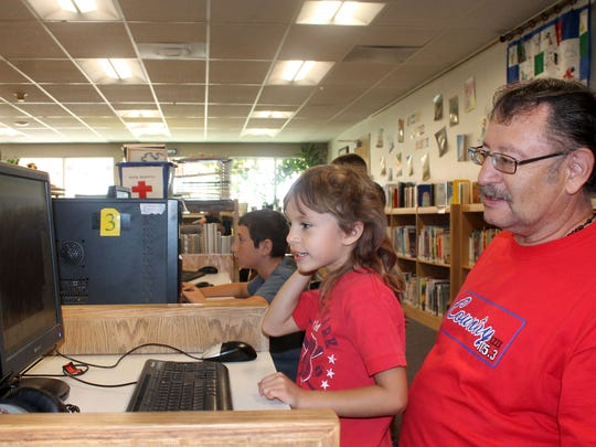 Tim and Debra Gutierrez, father and daughter, utilize one of the library's computers on Friday afternoon.
