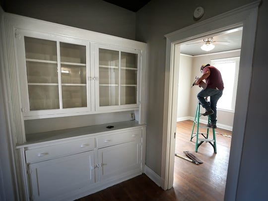 Joe Castnuela installs a new ceiling fan in a unit at the Broadmoor  apartments. Built-in cabinets and vintage molding are among the details being restored as part of a $500,000 renovation project.