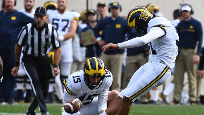 Oct 29, 2016; East Lansing, MI, USA; Michigan Wolverines place kicker Kenny Allen kicks a field goal as Garrett Moores holds against the Michigan State Spartans during the second half at Spartan Stadium.