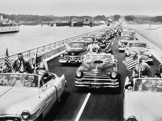 As a ferry leaves its slip, a motorcade crosses the new Chesapeake Bay Bridge after dedication, July 30, 1952.  In the lead cars are then-Maryland Gov. Theodore Roosevelt  McKeldin, Delaware Gov. Elbert Carvel, former Maryland Gov. William Preston Lane Jr. and their wives.  Prior to the completion of the bridge,  a ferry brought passengers and about 50 vehicles across the water, from Annapolis to Matapeake. The trip took about 45 minutes, although lines to get on board often backed up hours, especially in summer.
