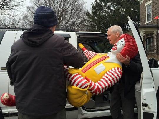 Ken Coleman, right, gets help lifting a Ronald McDonald statue out of his car to carry the statue to its new place at the Ronald McDonald House in Burlington on Tuesday.
