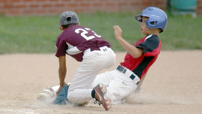 Boonville Ready Mix's  Brennan Alberts slides under the tag by Einspahr Construction pitcher Karson Elbert in the fifth inning Wednesday night in Cal Ripken Minor at the COCOBA ballfield. Einspahr Construction defeated Boonville Ready Mix 7-6 to capture the title in Cal Ripken Minor at 8-4.