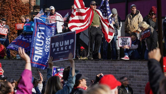 Michael Foy of Wixom holds his flag open while standing above the crowd gathered for a rally in support of President Trump outside of the TCF Center in Detroit on Friday, Nov 6, 2020 where the absentee ballot count for the city of Detroit took place.