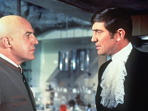 Telly Savalas, left, with George Lazenby as James Bond in