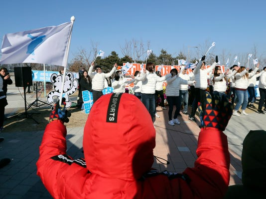 Supporters of combined Koreas women's ice hockey team wave the unification flags before the tune-up game between the combined Koreas team and Sweden prior to the 2018 Winter Olympics, outside of the ice rink in Incheon, South Korea, Sunday, Feb. 4, 2018. (AP Photo/Lee Jin-man)