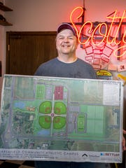 Scott Berg pictured with plans for a sports complex on Marshfield's south side.