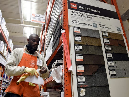 Prince Addy of Manassas, Va., straightens up the shelves of roofing products at the Home Depot in Falls Church, Va. Home Depot reported financial results on Feb. 20, 2018.