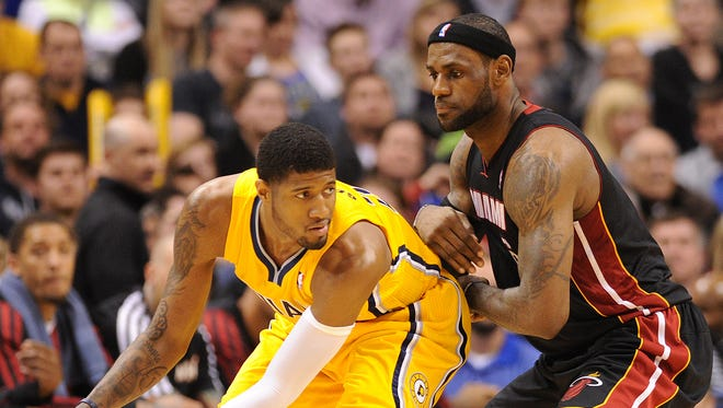 Indiana Pacers forward Paul George keeps the ball out of the reach of Miami Heat forward LeBron James inside Bankers Life Fieldhouse, March 26, 2014, in Indianapolis. The Pacers won the game 84-83.