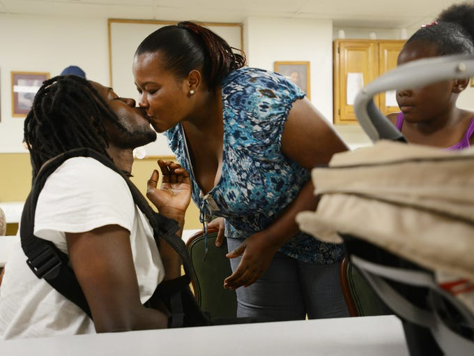 Tiana Jackson gives Lavar Bailey, her partner of seven years, a kiss hello in the morning.   6/18/14 - Erin Brethauer (ebrethau@citizen-times.com)