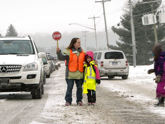 Rachael MacKenzie and her daughter Rebecca, 7, work as crossing guards at the intersection of Greyhound Drive and Iverness Street between Lockwood Elementary and Greyhound Intermediate School as part of a Girl Scout Troop 30031 Brownie Quest project, Wednesday afternoon, Feb. 4.