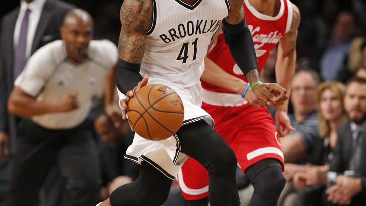 Brooklyn Nets forward Thomas Robinson dribbles down court with Memphis Grizzlies guard Courtney Lee in pursuit in the second half of an NBA basketball game, on in New York. The Grizzlies defeated the Nets 109-90.