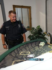 IMPD officer Steve Elliot and Sgt. Bill Carter look over the illegal gaming tables at 3469 N. College.