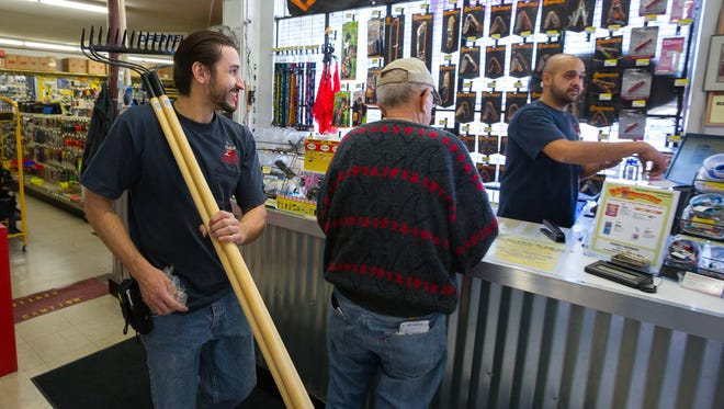 Hayden's Hardware employee Ian Lujan, left, carries a few rakes while store manager Adrian Gonzalez helps a customer.