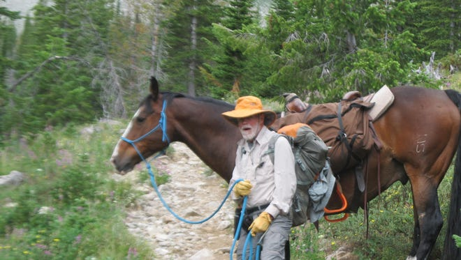 Ernie Vyse leading horse as he treks the Continental Divide trail in the Bob Marshall wilderness