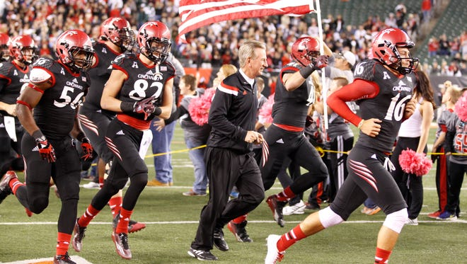 UC head coach Tommy Tuberville runs out with the team before the start of the Bearcats' game against USF on Friday.