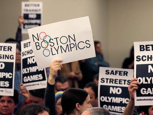 The audience hold up placards against the Olympic Games coming to Boston, during the first public forum regarding the city's 2024 Olympic bid, in Boston on Thursday, Feb. 5, 2015, (AP Photo/Charles Krupa)