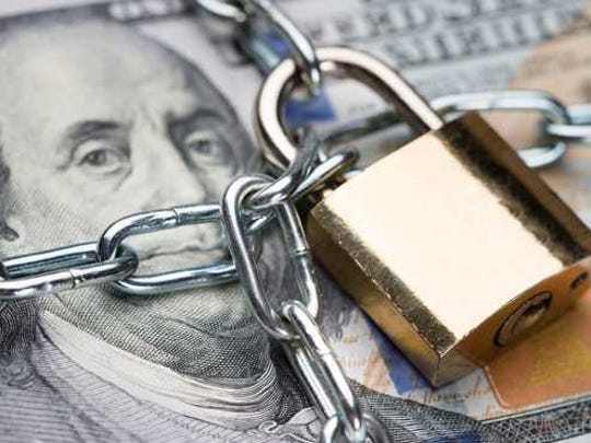 Chain and padlock on a bundle of cash.