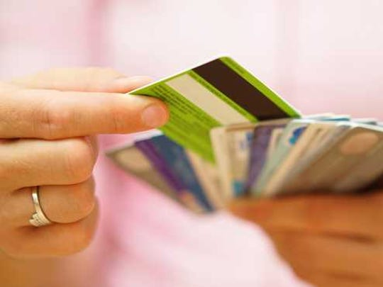 A woman holding about 10 credit cards in her hand and choosing one.