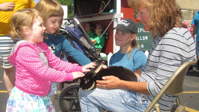 Charlotte Estes, 3, and her sister, Isabelle, 5, of Fond du Lac, were excited petting a 1-year-old Rex breed rabbit brought to the annual dairy month petting zoo at the National Exchange Bank and Trust on June 6 by Sylvia Ford and her mom of the Weeping Willow 4-H Club.