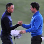 Rickie Fowler of the U.S. (left) shakes hands with Rory McIlroy on the 18th green at the end of their halved foursome.