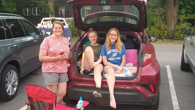 The Dube family gets ready to watch a movie in the parking lot of the Paul Memorial Library.