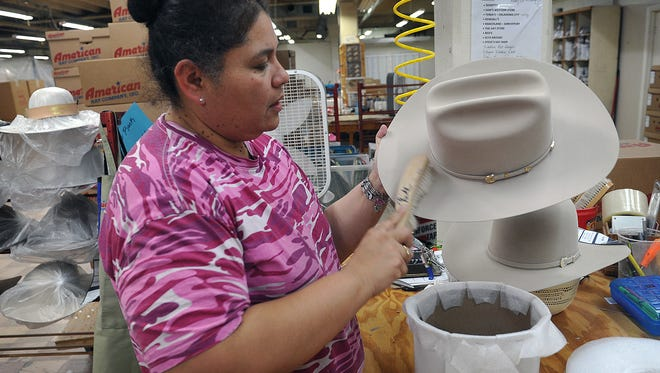 Helen Romo, an inspector for the American Hat Company in Bowie, puts the finishing touches on a cowboy hat made for President-elect Donald Trump. The light grey felt hat has a cattleman crown and a J brim style.