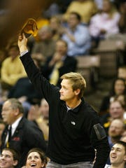 Former Hawkeye place kicker Nate Kaeding acknowledges crowd after being introduced during first half of Iowa's basketball game in 2009 against Wisconsin.
