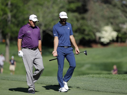 Phil Mickelson, left, talks with Dustin Johnson as they walk down the 13th fairway during the first round of the Memorial golf tournament, Thursday, June 1, 2017, in Dublin, Ohio. (AP Photo/Darron Cummings)