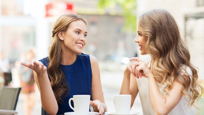 Two women share coffee and catch up in this stock photo.