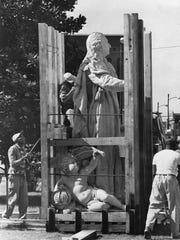 Workers unpack the marble statue of King Louis XVI