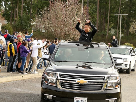 North Kitsap boys basketball player Kobe McMillian waves during a rally for the school's state tournament-bound basketball teams on Tuesday.