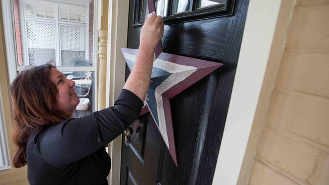 Melissa Marsh, who lives on Du Pont Street near St. Anthony of Padua in Wilmington, decorates her front door with a patriotic star.