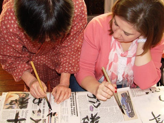 A volunteer instructor with the Mid-Hudson Japanese Community Association demonstrates calligraphy to a participant as part of the Kakizome program in January 2013.