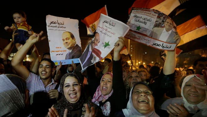 Supporters of Abdel Fattah al-Sisi, Egypt's former military chief, hold his posters during a celebration at Tahrir Square in Cairo on May 29.