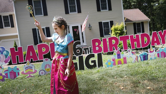 Gigi Schmidt, who is turning 6, plays around a surprise display of birthday cards in front of her home in Cohasset on Wednesday August 19, 2020. Greg Derr/The Patriot Ledger