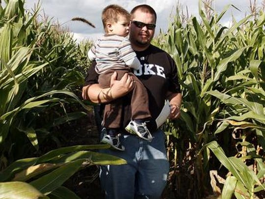 Joe Wiater and his one year-old son Nathan Wiater, both of Wausau, take a tour through the corn maze at Willow Springs Garden off from Hillcrest Dr. in Wausau.