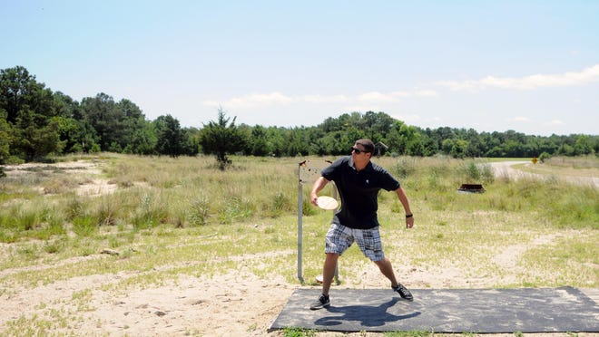 Sports reporter Ryan Marshall backhands a disc at the Cape Henlopen State Park disc golf course. This was one of his few good throws.